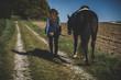 Junge schöne Frau und schwarzes Pferd Ausritt, reiten, Derssur, Reiterin