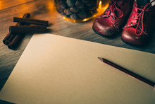 New Year Resolutions For Children. Writing Letter To Santa. Blank Letter With Baby Shoes, Cinnamon, Pencil On A Wooden Table. Copyspace Included.
