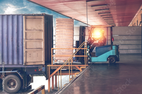 Fotografia  Forklift handling empty tin cans from container into warehouse