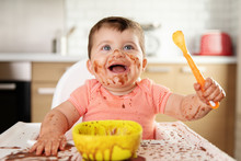 Happy Baby With Messy Face Eating Chocolate Dessert With Spoon