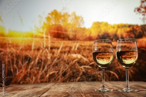 Two glasses with wine on a wooden table in an autumn setting