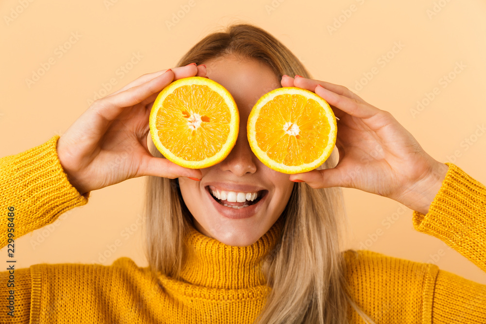 Fototapeta Beautiful woman covering eyes with citrus lemons posing isolated over yellow wall background.