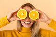 Beautiful woman covering eyes with citrus lemons posing isolated over yellow wall background.