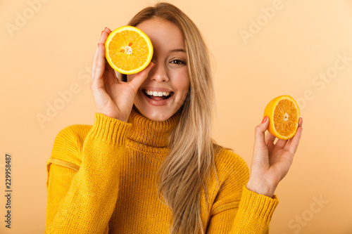 Fotografia Beautiful woman covering eyes with citrus lemons posing isolated over yellow wall background