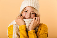 Happy Cute Woman Wearing Scarf And Hat Posing Isolated Over Yellow Wall Background.