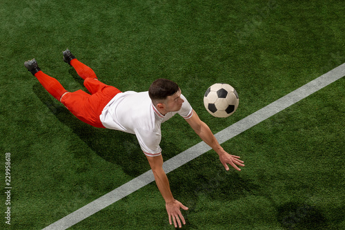 Staande foto Voetbal Football player tackling for ball over green grass background. Professional football soccer player in motion at studio. Fit jumping man in action, jump, movement at game.