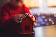 Children's hands holding Christmas toy red house with garland bokeh background indoor at home.