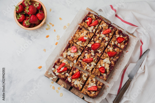 Foto op Canvas Kruidenierswinkel Dessert Squares with Strawberries and Oat Streisel on light concrete background. Rustik style. Top view.