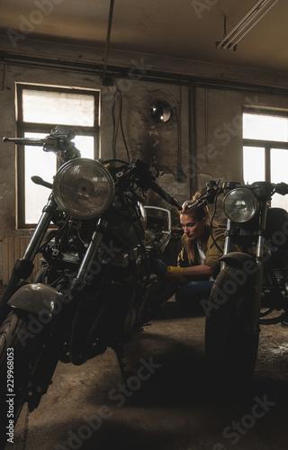 Fotobehang Fiets Young female working on restoration of old /vintage motorbikes in old rusty motorbike garage/workshop