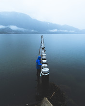 A Young Person Walks Along A Wooden Structure Above The Water On A Rainy And Foggy Day In Squamish BC