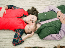 Couple Laying On A Blanket Together And Looking Up At Camera