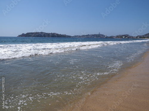 Fotografija  Scenic scenery of sandy beach at bay of ACAPULCO city in Mexico and white waves