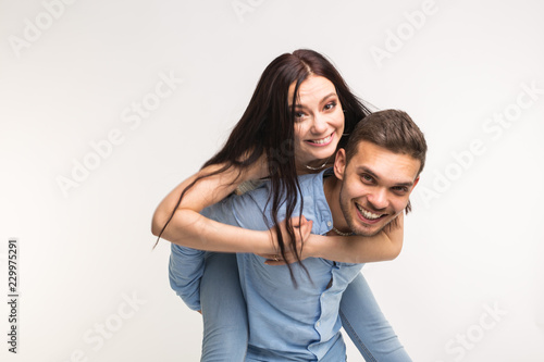 Photo  Fun and relationship concept - Man carrying girlfriend on his back on white back