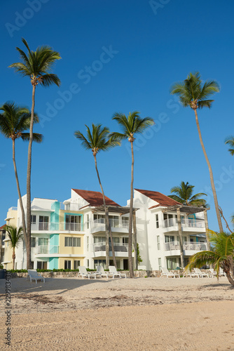 Foto op Canvas Strand Photo of multy-family coast houses near Atlantic Ocean on beach of Bavaro. Lots of palm trees are planted near house. Roofs of the buildings are darker than facades and are made of terracotta tiles.