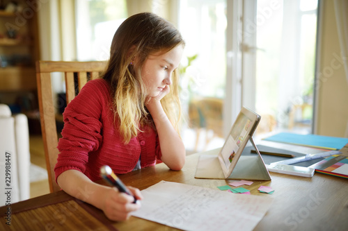 Obraz Smart schoolgirl doing her homework with digital tablet at home. Child using gadgets to study. Education and learning for kids. - fototapety do salonu
