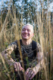 Fototapeta Łazienka - Side view portrait of a young attractive bearded blonde guy sitting and smiling on the field grass on trees background.