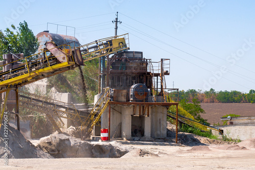 Fotografía  Crushing machinery, cone type rock crusher, conveying crushed granite gravel stone in a quarry open pit mining