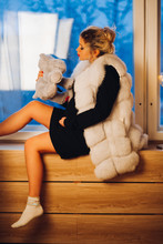 Side View Of Blonde Woman In Fur Vest Kissing Hippo Toy Sitting By The Window With Modern Electric Lamp.