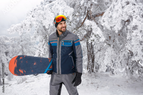 young male snowboarder with snowboard on winter holiday in the mountain