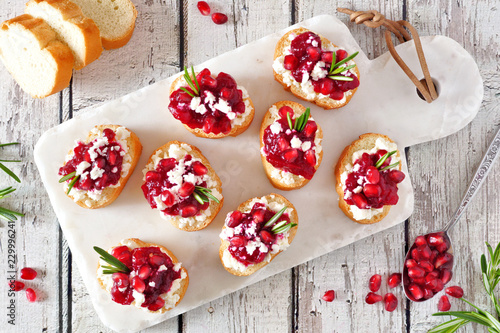 Holiday crostini appetizers with cranberries, pomegranates and feta cheese. Above table scene on a white platter.