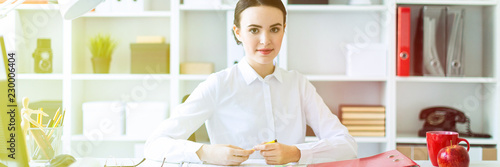 Fotografia  A young girl in the office sits at a table and holds a pen in her hands