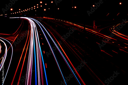 Photographie  Cars light trails on a curved highway at night