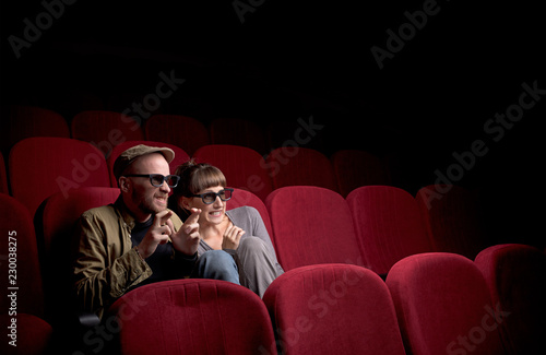Fotografija  Young cute couple sitting alone at red movie theatre and having fun