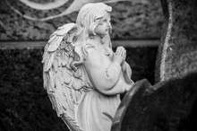 Closeup Of Stoned Angel Praying On Tomb At Cemetery