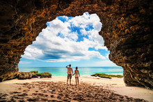 A Loving Couple Enjoying The Breathtaking Views Of The Tropical Sandy Beach And Sea From Mountain Cave