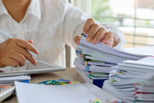 Teacher Hand Is Searching Student Report And Homework Assignment On Desk In School For Score. Unfinished Paperwork Stacked In Archive With Color Papers And Paper Clips. Education And Business Concept.