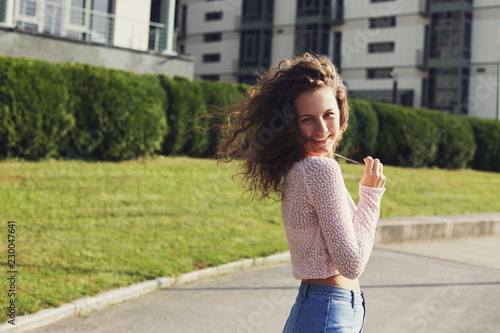 Fényképezés  Outdoor shot of attractive confident, happy curly headed woman with long natural hair, smiling broadly at camera, walking along park and enjoying warm summer day, flirting with boyfriend who captures
