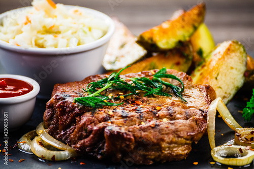 Grilled steak with baked potatoes and vegetables served on black stone on wooden table