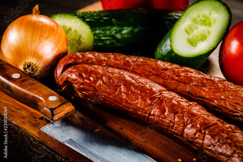 Raw sausages with vegetables on cutting board