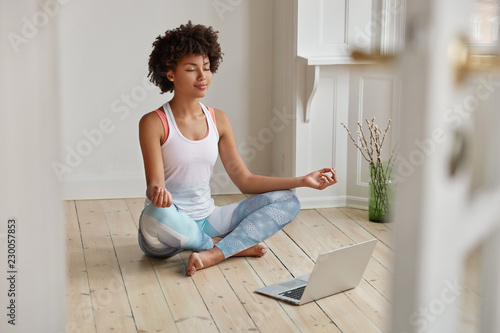 Fotografia Relaxed dark skinned woman with sporty body, sits in zen pose, keeps legs crossed, watches yoga lessons on laptop computer using internet, meditates on floor in empty room