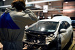 frustrated stressed mechanic man in white uniform holding head against car in repair garage