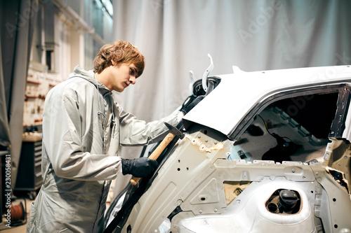 Photo auto garage worker flatten metal body car with hammer in automotive garage
