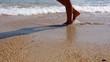 People legs walking along sea shore on summer sunny tropical beach
