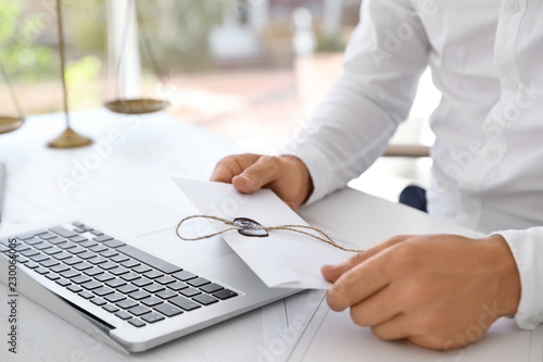 Male notary with sealed document at table in office, closeup Canvas Print