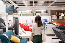 Young Woman Choosing Furniture In A Modern Home Furnishings Store