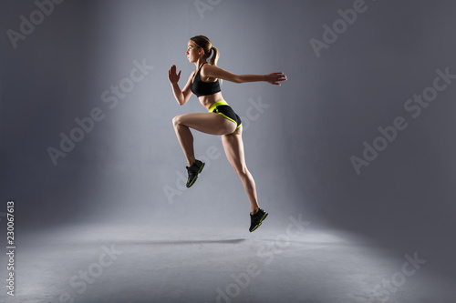 Side view tightened fit beautiful athlete jumps in a sports suit during cardio exercise. Concert of endurance and fat burning