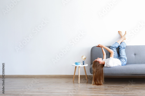 Stampa su Tela Young beautiful woman wearing white t-shirt on grey textile sofa at home