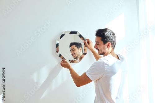 Fotografía  Studio portrait of young man standing near wall and hang mirror