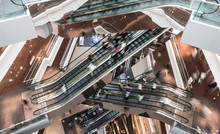 Customers Clients Moving On Escalator Staircases Inside Of Giant Modern Shopping Mall. Consumption Concept.