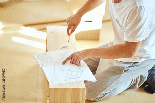 Concentrated young man reading instructions to assemble furniture at home Tableau sur Toile