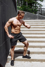 A Hot, Sexy Young Man With Muscular Naked Body Training Outdoors. Handsome Sportive Runner Exercising On Staircase In Summer Morning, Increasing Then Slowing Down, Looking At Wristwatch.