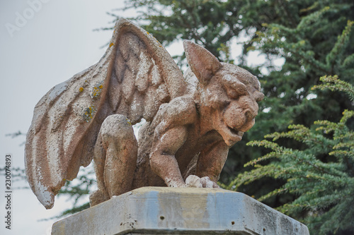 Fotografia, Obraz Image of a stone gargoyle sitting on top of a column with wings raised in San Ma