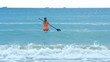 back view girl paddles board sitting on knees to open ocean