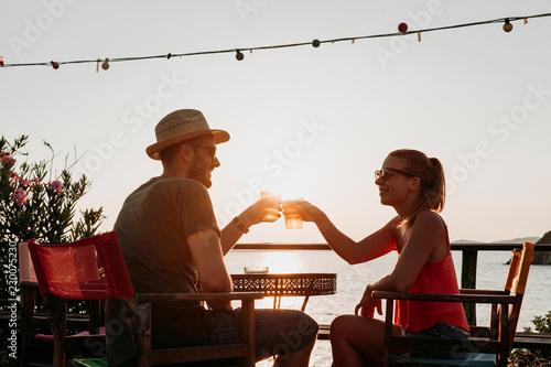 Foto  Couple enjoying sunset in a beach bar drinking beer