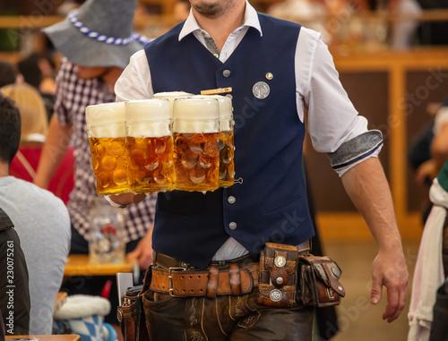 Oktoberfest, Munich, Germany. Waiter serving beers, closeup view Poster Mural XXL