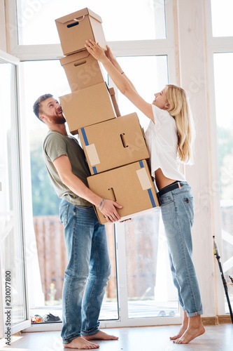 Fotomural  blonde female placing moving boxes on large stack man is holding all